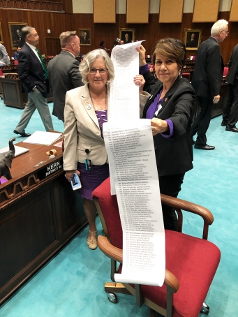 Minority Leader Charlene Fernandez and Rep. Pamela Powers Hannley hold a list of Arizona voters who supported ratification of the ERA on the Legislature's Request to Speak System.